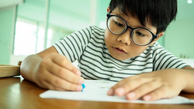 Asiatische hübsche jungenzeichnung und -farbton im klassenzimmer
