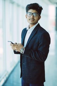 Asiatische indische geschäftsleute, die unter verwendung des smartphones beim gehen im modernen büro sms schreiben