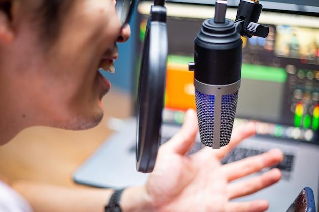 Asiatische influencer verwenden mikrofon für podcasts und nehmen ton auf, um eine datei in das system hochzuladen. live-aufnahme. online sprechen mit mobile. studio-audioübertragung.