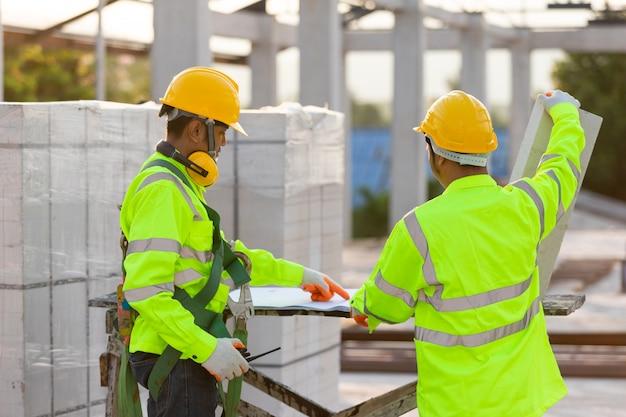 Asiatische ingenieure und arbeiter berieten sich gemeinsam bei der bauplanung und -entwicklung, konzept der bauteamarbeit.