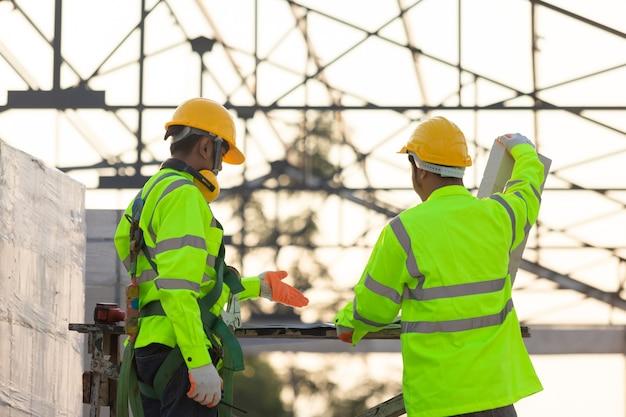 Asiatische ingenieure und arbeiter, die gemeinsam für den hintergrund der bauplanung und -entwicklung konsultiert wurden, sind die dachkonstruktion und das konzept der arbeit des bauteams.