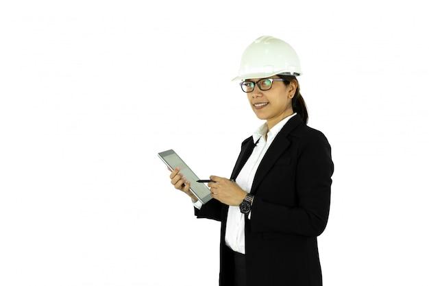 Asiatische ingenieurfrau im weißen sturzhelm unter verwendung der tablette, lokalisiert auf weiß.