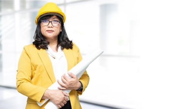 Asiatische ingenieurin, die im büro mit kopienraum steht.