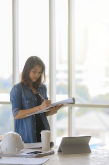 Asiatische ingenieurin in blauem jeanshemd, die auf der baustelle mit weißem helm steht