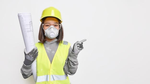 Asiatische ingenieurin trägt schutzhelm-schutzhandschuhe und maske hält baupläne zeigt weg auf leerzeichen zeigt projekt