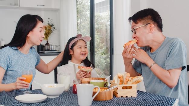 Asiatische japanische familie frühstückt zu hause. asiatische mutter, vati und tochter, die glücklich sich fühlen, zusammen zu sprechen, während brot, corn flakes getreide und milch in der schüssel auf tabelle in der küche morgens essen.