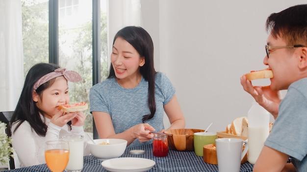 Asiatische japanische familie frühstückt zu hause. die asiatische glückliche mutter, die erdbeermarmelade auf brot für tochter macht, essen corn flakes getreide und milch in der schüssel auf tabelle in der küche morgens.