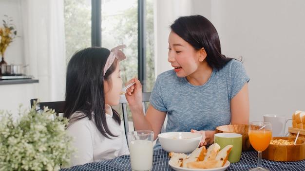 Asiatische japanische familie frühstückt zu hause. glückliche unterhaltung der asiatischen mutter und der tochter beim essen des brotes, des orangensaftes, des corn flakesgetreides und der milch auf tabelle in der modernen küche am morgen.