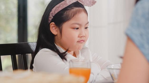 Asiatische japanische tochter mit essen gelangweilt. lebensstil scherzt traurige abneigung gegen umgekippte frühstücksmahlzeit des lebensmittels in der modernen küche am haus morgens.