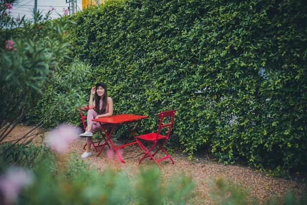 Asiatische jüngere frau, die im grünen park sitzt