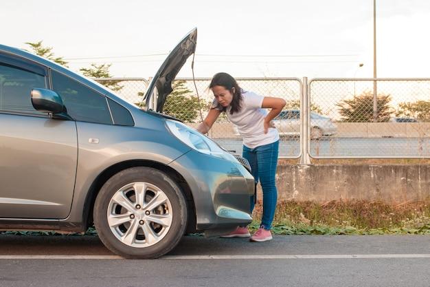 Asiatische jugendfrauen, die einen handy anhalten um das auto gehen, stressige stimmung während der abendstunden. entlang der autobahn weil ihr auto kaputt gegangen ist und sie auf die hilfe von jemandem wartet.