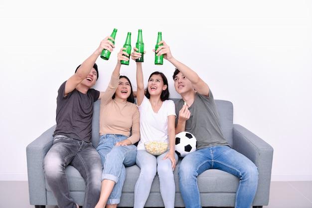 Asiatische jugendliche, die fußball im fernsehen aufpassen