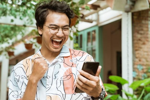 Asiatische jugendliche, die handys halten und anschauen, sind sehr glücklich