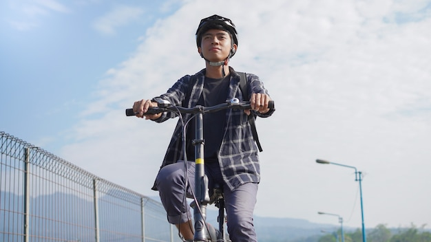 Asiatische jugendliche fahren mit dem fahrrad zur arbeit
