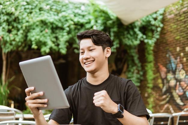 Asiatische jugendliche schauen auf den tablet-bildschirm und lachen dann