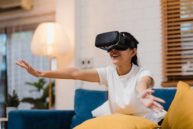 Asiatische jugendlichfrau, die den simulator der virtuellen realität der gläser spielt videospiele im wohnzimmer verwendet