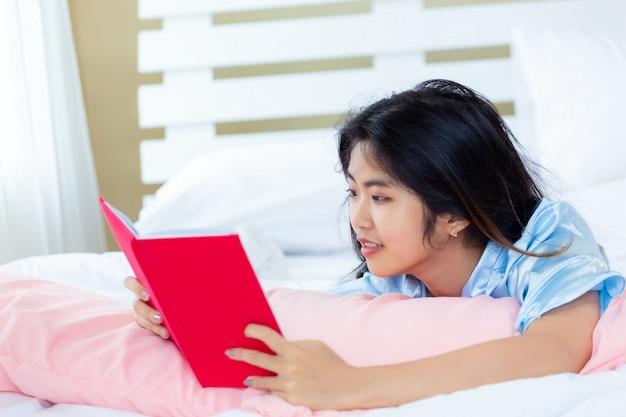 Asiatische jugendlichfrau las tagebuchbuch auf dem bett
