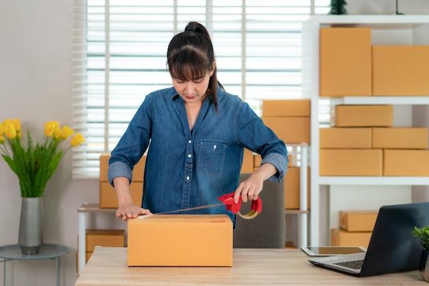 Asiatische jugendlichinhaber-geschäftsfrau arbeiten zu hause für das on-line-einkaufen und wickeln produkte mit braunen kästen für lieferungspostversand mit büroausstattung, unternehmerlebensstilkonzept ein