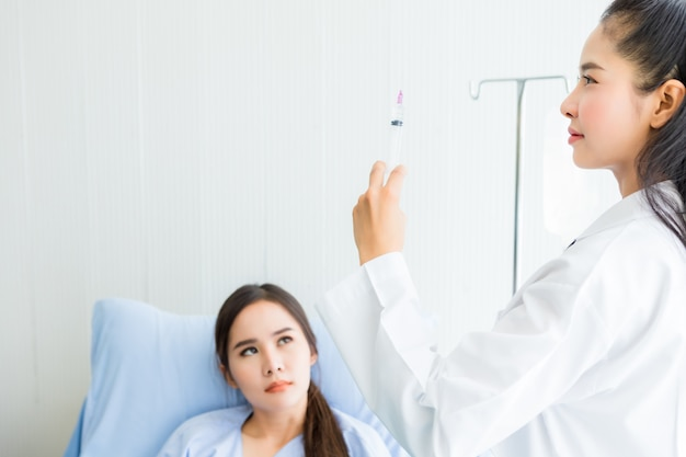 Asiatische junge ärztin mit spritze zum asiatischen jungen weiblichen patienten auf bett für das bessere heilen im raumkrankenhaus