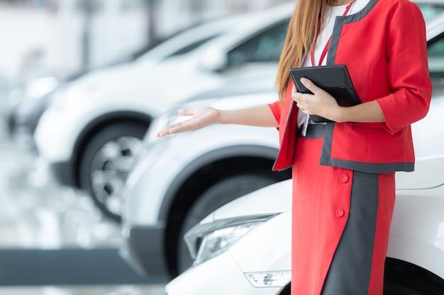 Asiatische junge autoverkäuferin, die taschenrechner mit einer willkommenen anzeige im ausstellungsraum hält.