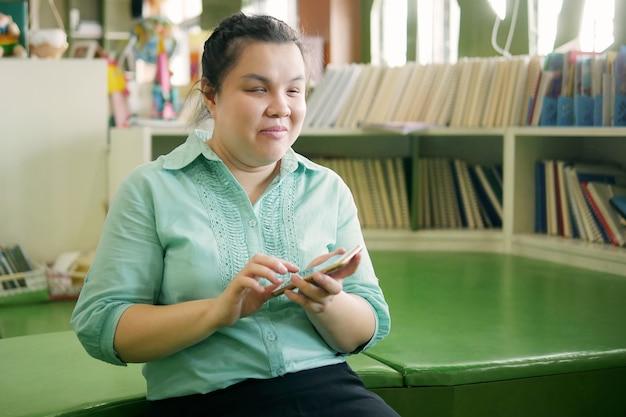 Asiatische junge blinde frau, die smartphone mit sprachzugang für personen mit behinderungen am kreativen arbeitsplatz verwendet.