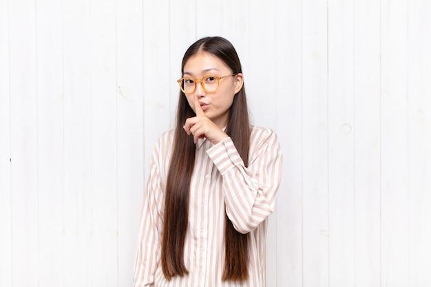 Asiatische junge frau bittet um stille und ruhe, gestikuliert mit dem finger vor dem mund, sagt shh oder hält ein geheimnis