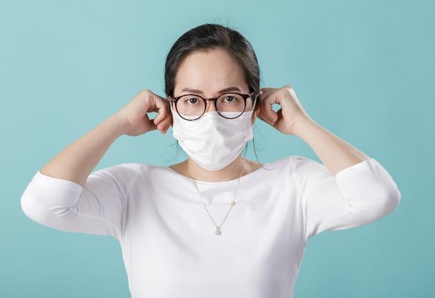 Asiatische junge frau, die atemschutzmaske trägt