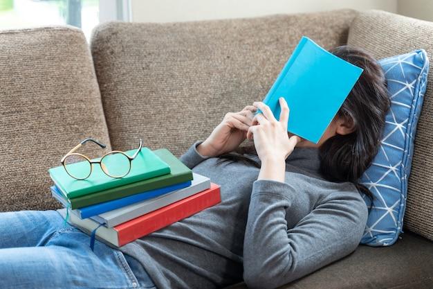 Asiatische junge frau, die auf couch schläft, während stapel bücher auf ihren körper gesetzt