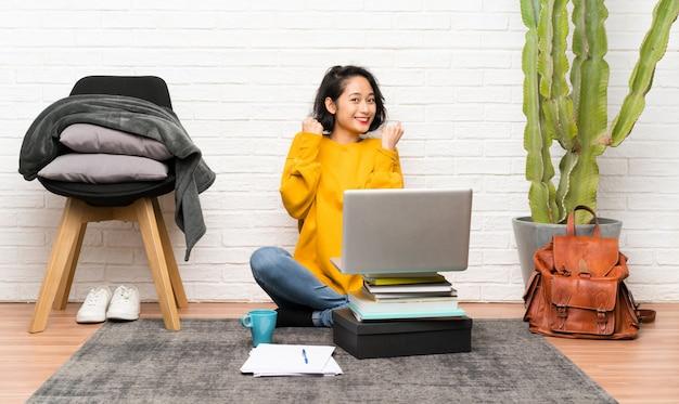 Asiatische junge frau, die auf dem boden feiert einen sieg sitzt