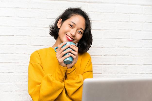 Asiatische junge frau, die auf dem boden hält einen tasse kaffee sitzt