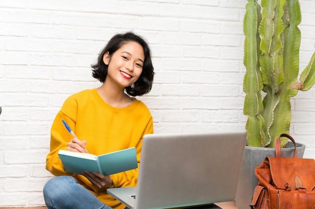 Asiatische junge frau, die auf dem boden sitzt