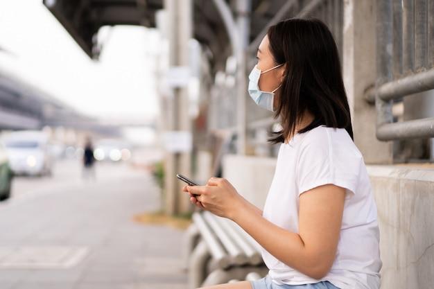 Asiatische junge frau, die auf den bus an der bushaltestelle in der überfüllten stadt wartet