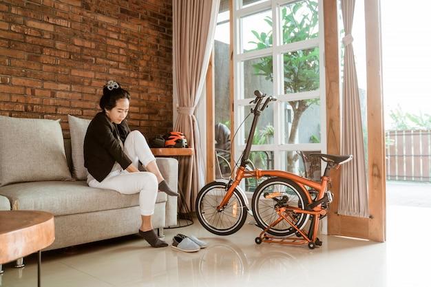 Asiatische junge frau, die auf der couch sitzt und socken trägt, wenn sie sich auf die arbeit vorbereiten