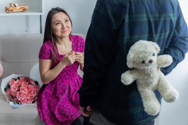 Asiatische junge frau, die auf einer couch mit blumenstrauß glücklich und aufgeregt sitzt, während teddybär als geschenk empfängt