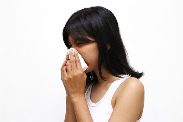 Asiatische junge frau, die auf weiß lokalisiert niest oder hustet
