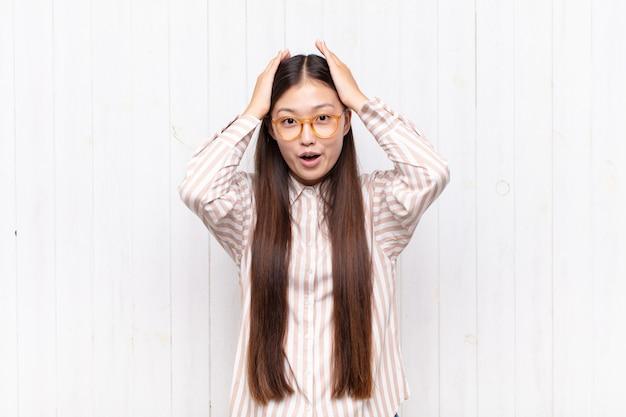 Asiatische junge frau, die aufgeregt und überrascht lokalisiert schaut