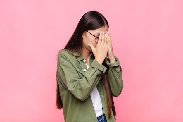 Asiatische junge frau, die augen mit händen mit einem traurigen, frustrierten blick der verzweiflung, des weinens, der seitenansicht bedeckt