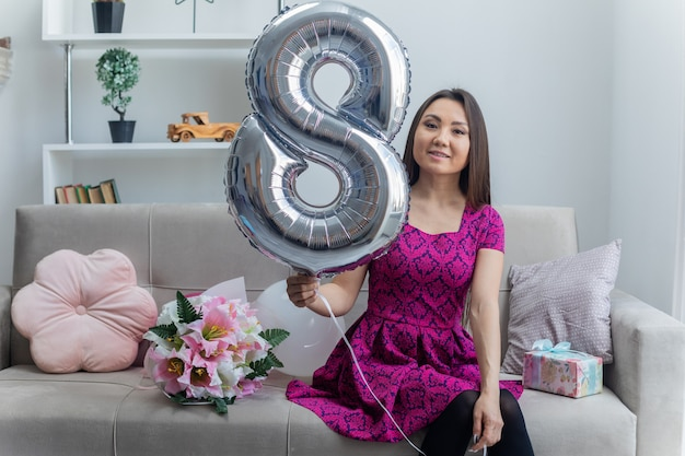 Asiatische junge frau, die ballon nummer acht hält, der auf einer couch sitzt
