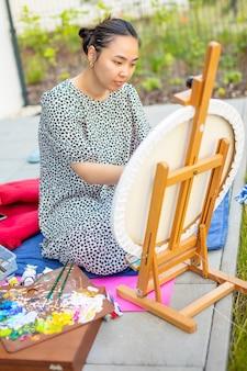 Asiatische junge frau, die bild in der heimterrasse malt