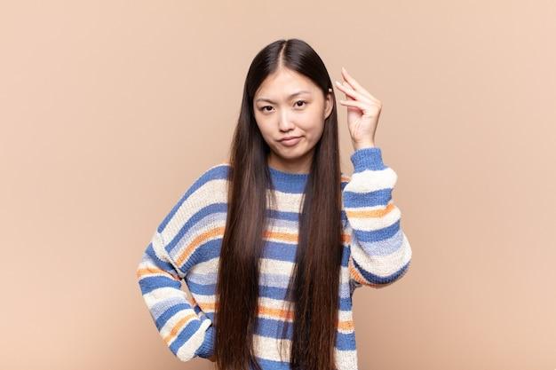 Asiatische junge frau, die capice oder geldgeste lokalisiert macht