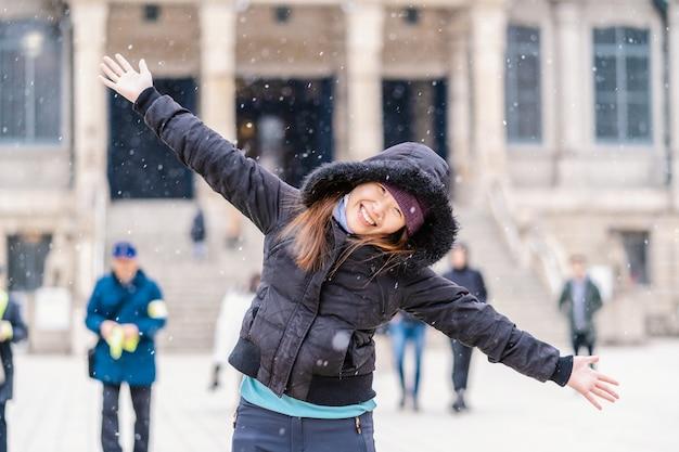 Asiatische junge frau, die den schnee spielt, als schnee gerade fiel, reise und aufgeregtes konzept