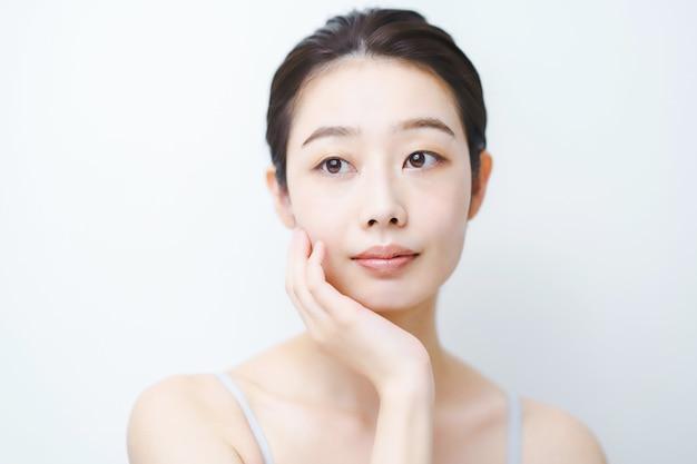 Asiatische junge frau, die den zustand ihrer haut überprüft