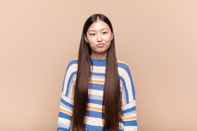 Asiatische junge frau, die doof und lustig mit einem albernen schielenden ausdruck aussieht, scherzend und herumalbern