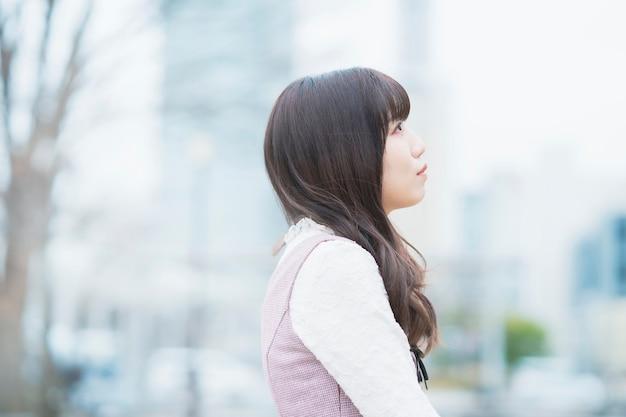 Asiatische junge frau, die draußen deprimiert aussieht