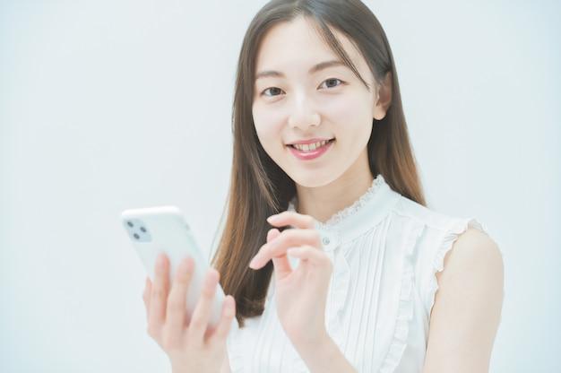 Asiatische junge frau, die ein smartphone bedient