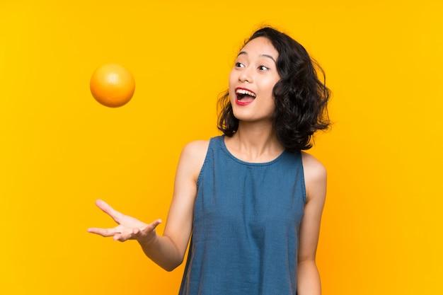 Asiatische junge frau, die eine orange anhält