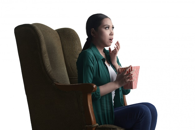 Asiatische junge frau, die einen horrorfilm aufpasst und popcorn mit dem sitzen auf dem sofa isst
