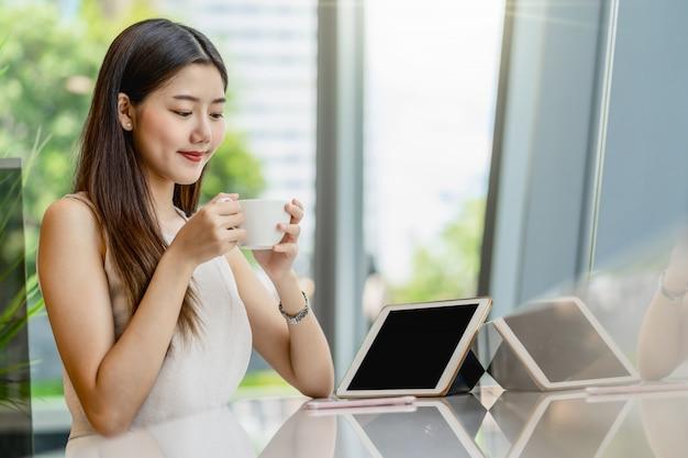 Asiatische junge frau, die einen tasse kaffee hält und tablette in der modernen kaffeestube oder im coworkingraum neben fensterspiegel, japaner, chinesen, koreanischem lebensstil und alltagsleben, unternehmerkonzept schaut