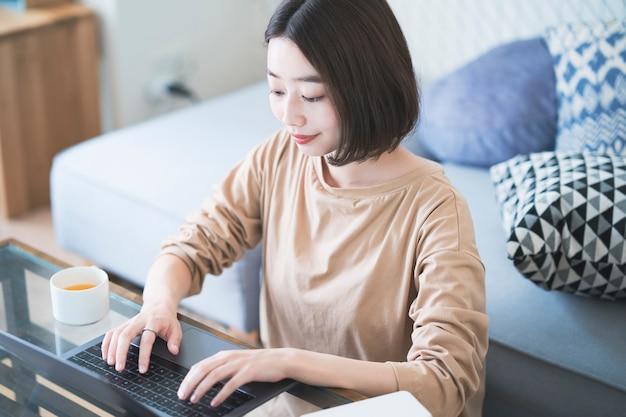 Asiatische junge frau, die entfernt im hauptzimmer arbeitet