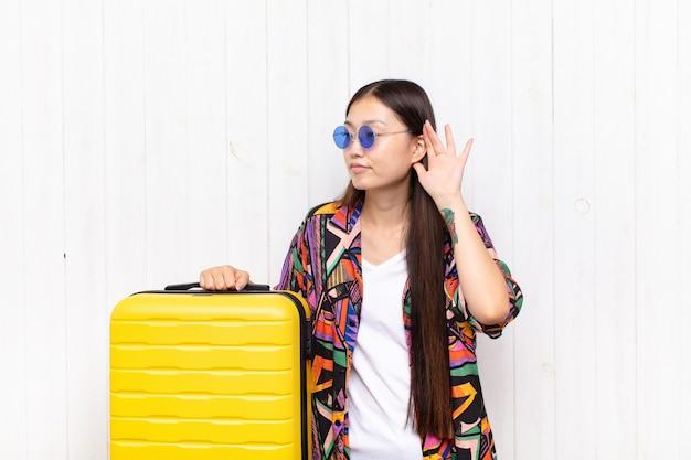 Asiatische junge frau, die ernst und neugierig aussieht, zuhört, versucht, ein geheimes gespräch oder klatsch zu hören, lauscht. urlaubskonzept